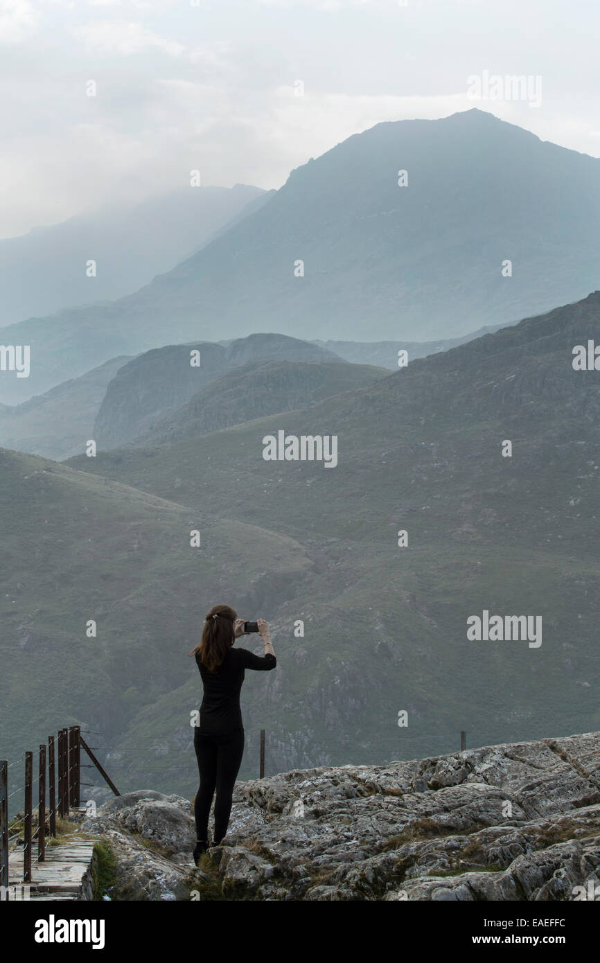 A young lady dressed in black is photographing mount snowdon with a camera phone. Stock Photo