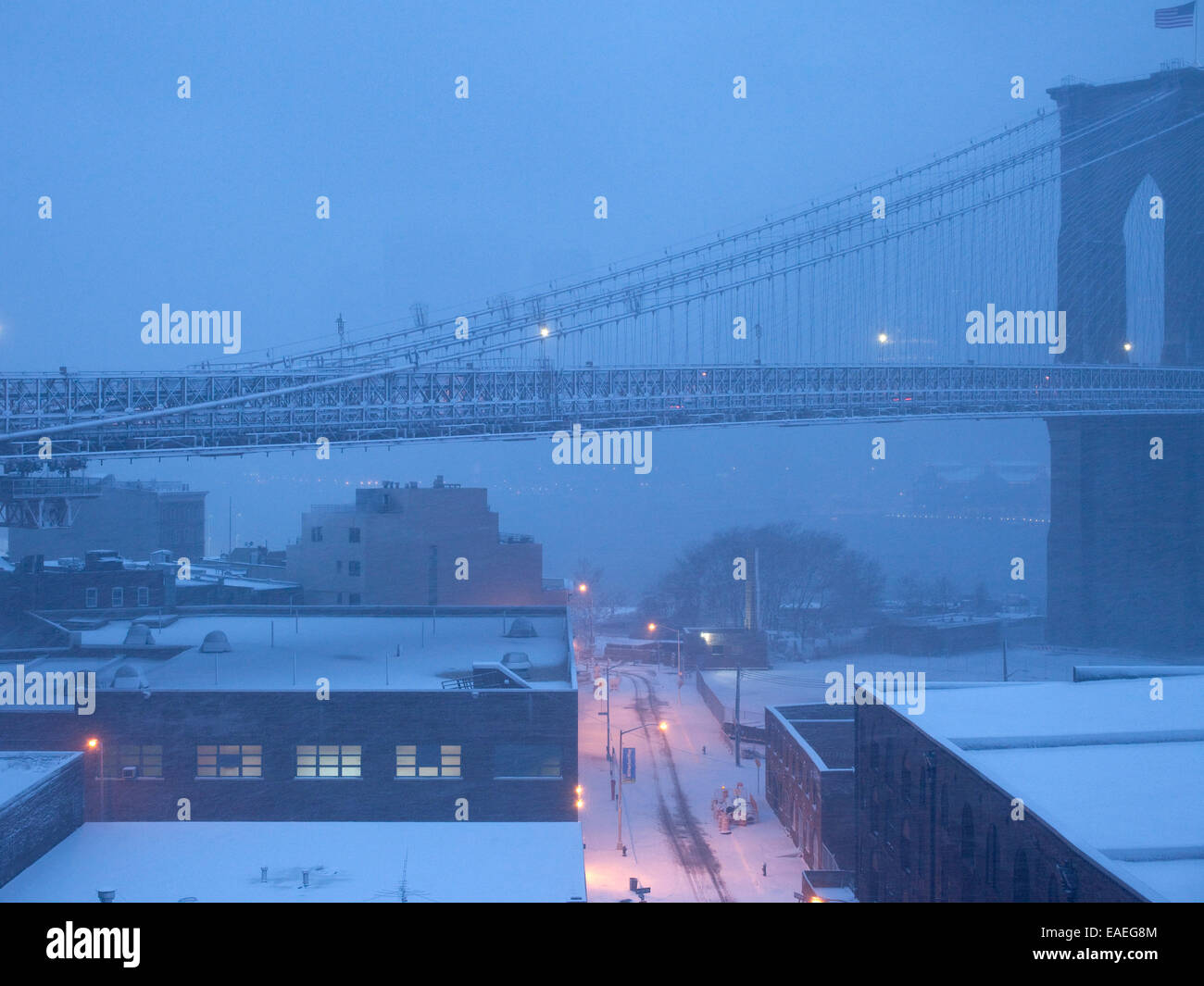 span of Brooklyn Bridge at dusk with fog and snow - Stock Image