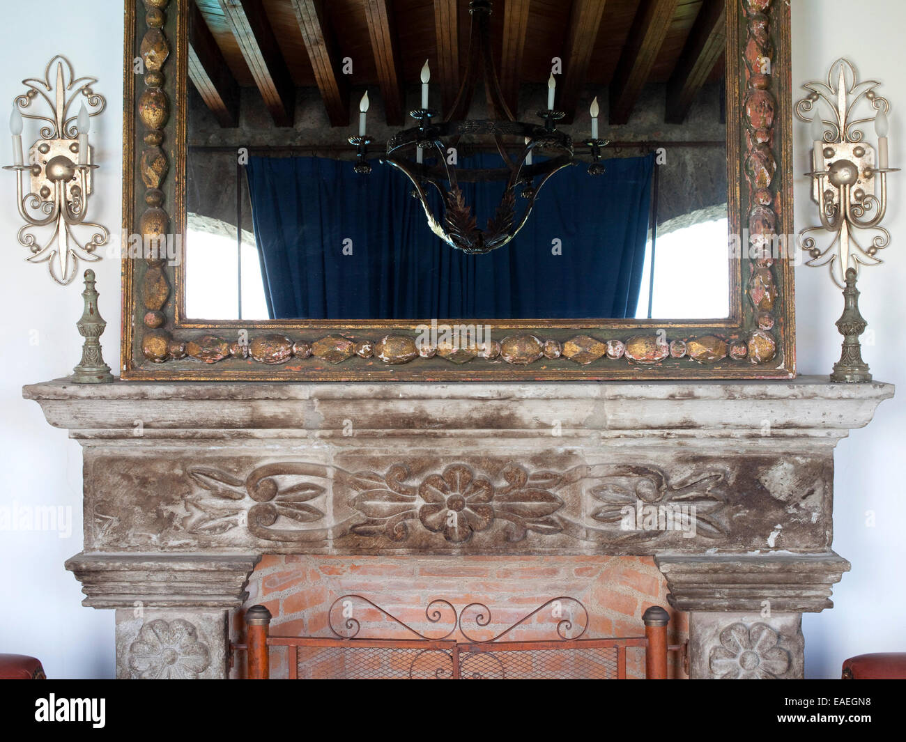 decorative gilded mirror and limestone fireplace with mantle - Stock Image