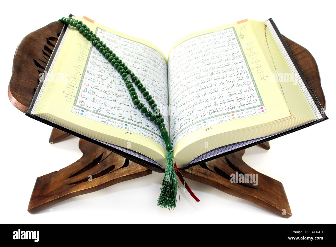 Quran with Quran wooden stand in front of white background - Stock Image