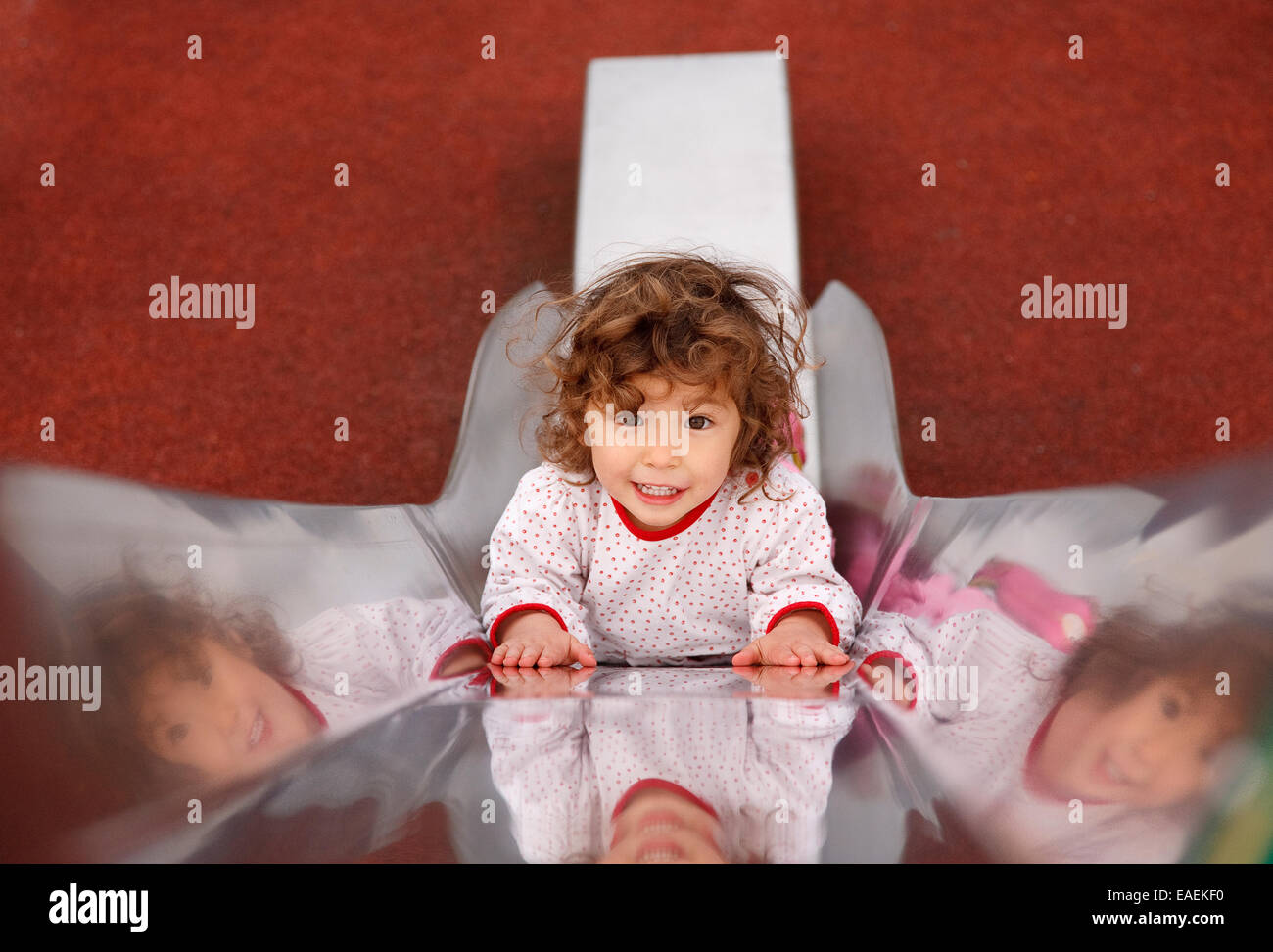 A two year old toddler girl on a slide - Stock Image