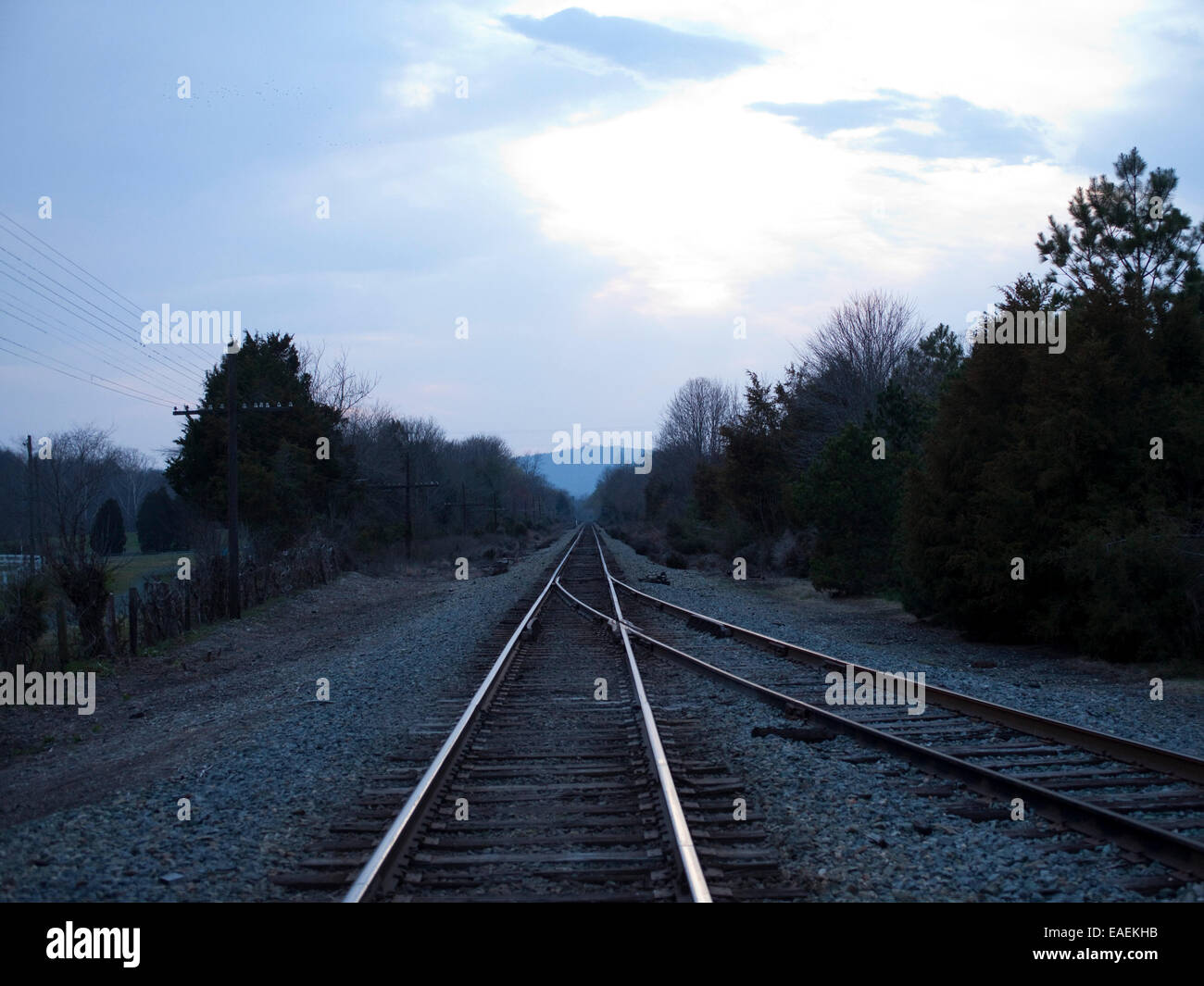train tracks at dusk receding in the rural countryside. - Stock Image
