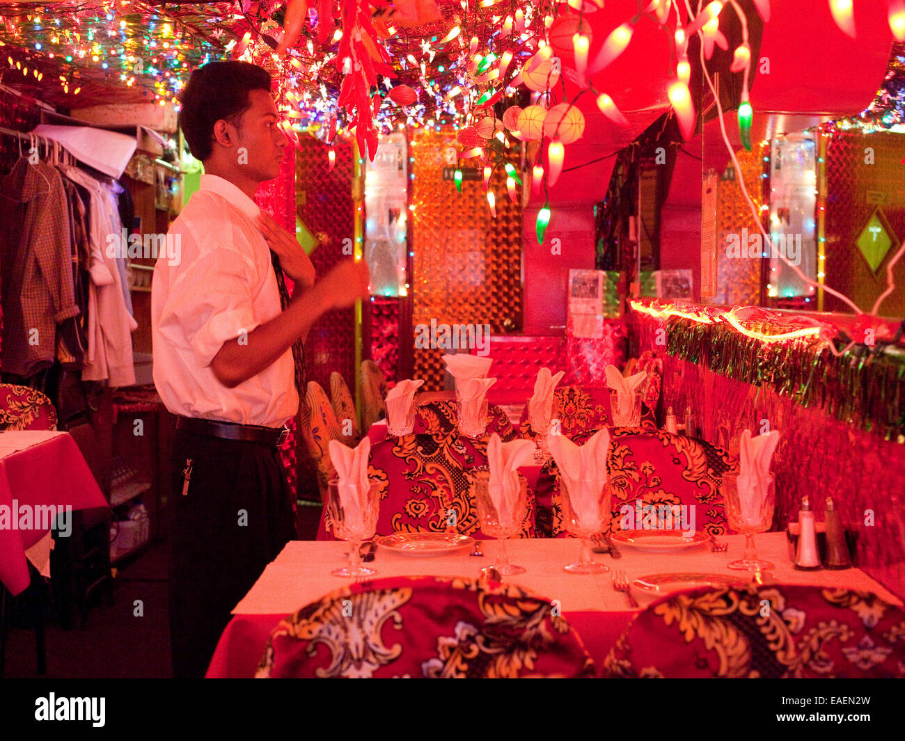 Waiter fixing his tie at Indian restaurant - Stock Image