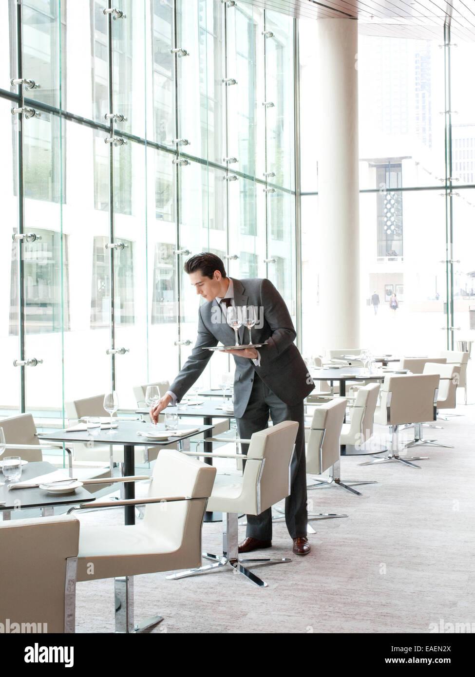 waiter setting table in upscale restaurant - Stock Image