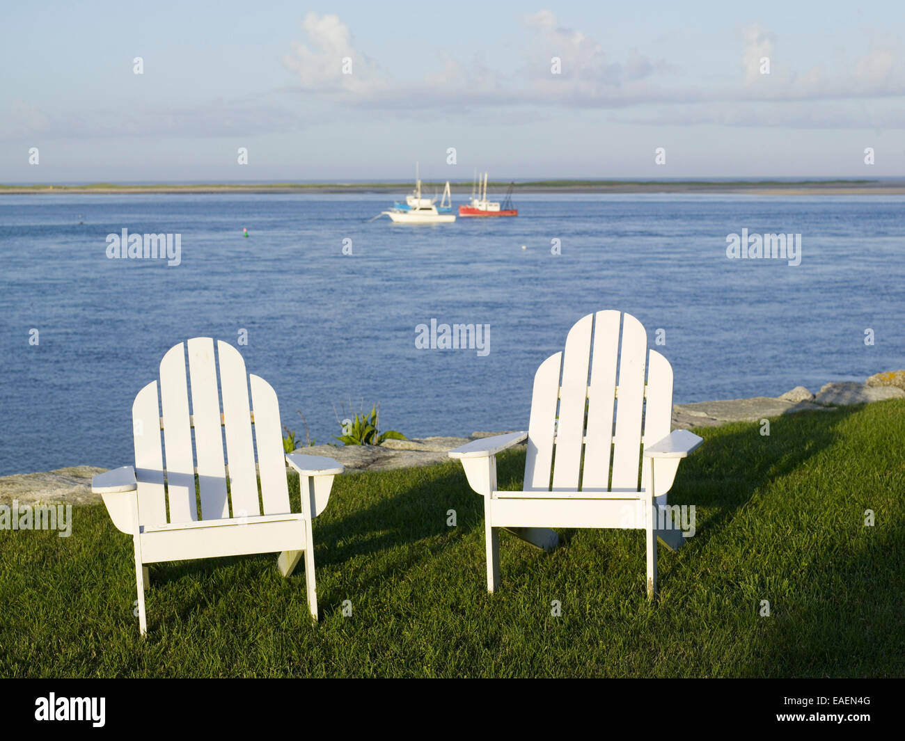 two white Adirondack chairs on lawn by the bay - Stock Image