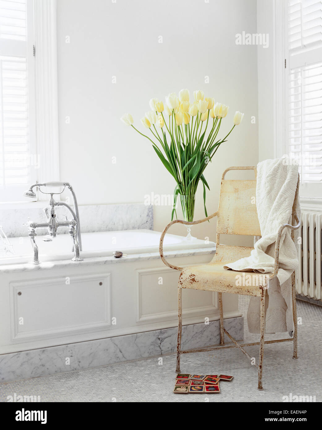 modern shabby chic white bathroom with marble, white tulips and old garden chair - Stock Image