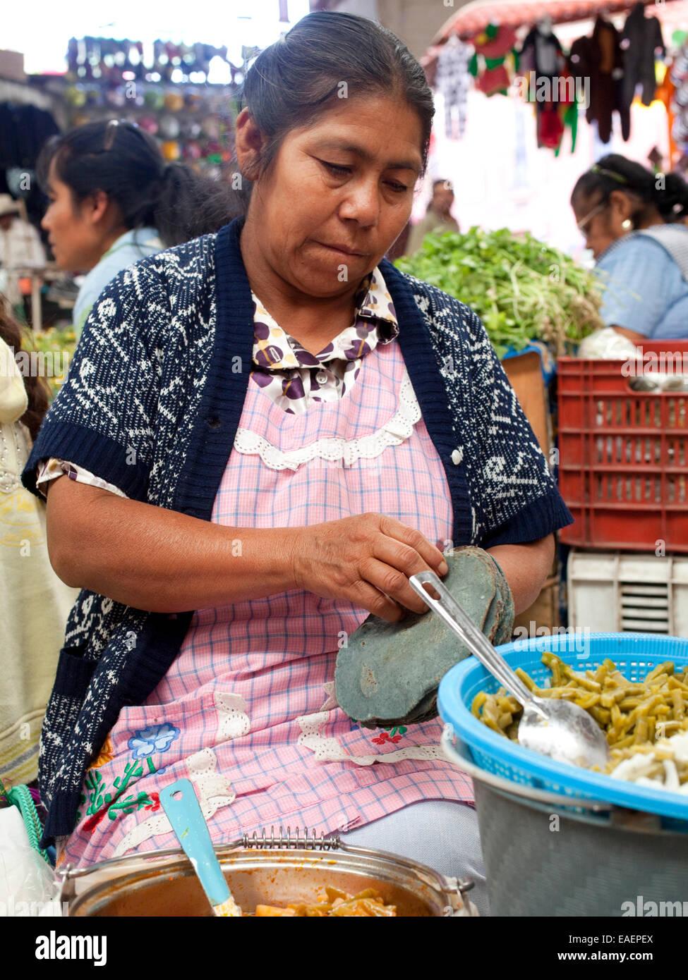 A woman peeling apart blue corn Tortillas at a market in Mexico - Stock Image