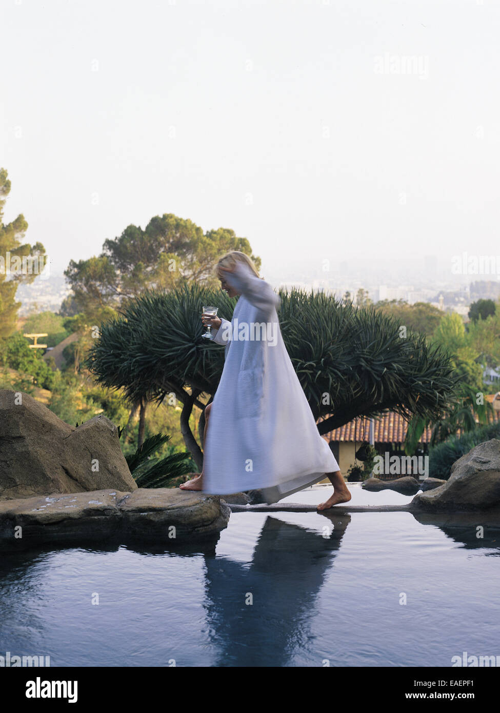 woman in white terry clothe robe walking across a swimming pool with a glass of wine in hand. - Stock Image