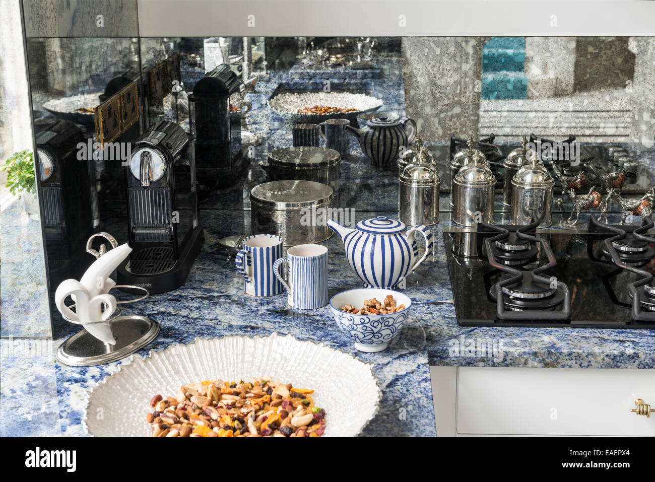 Nuts and fruit in dish on marbled kitchen countertop with hob and striped mugs - Stock Image