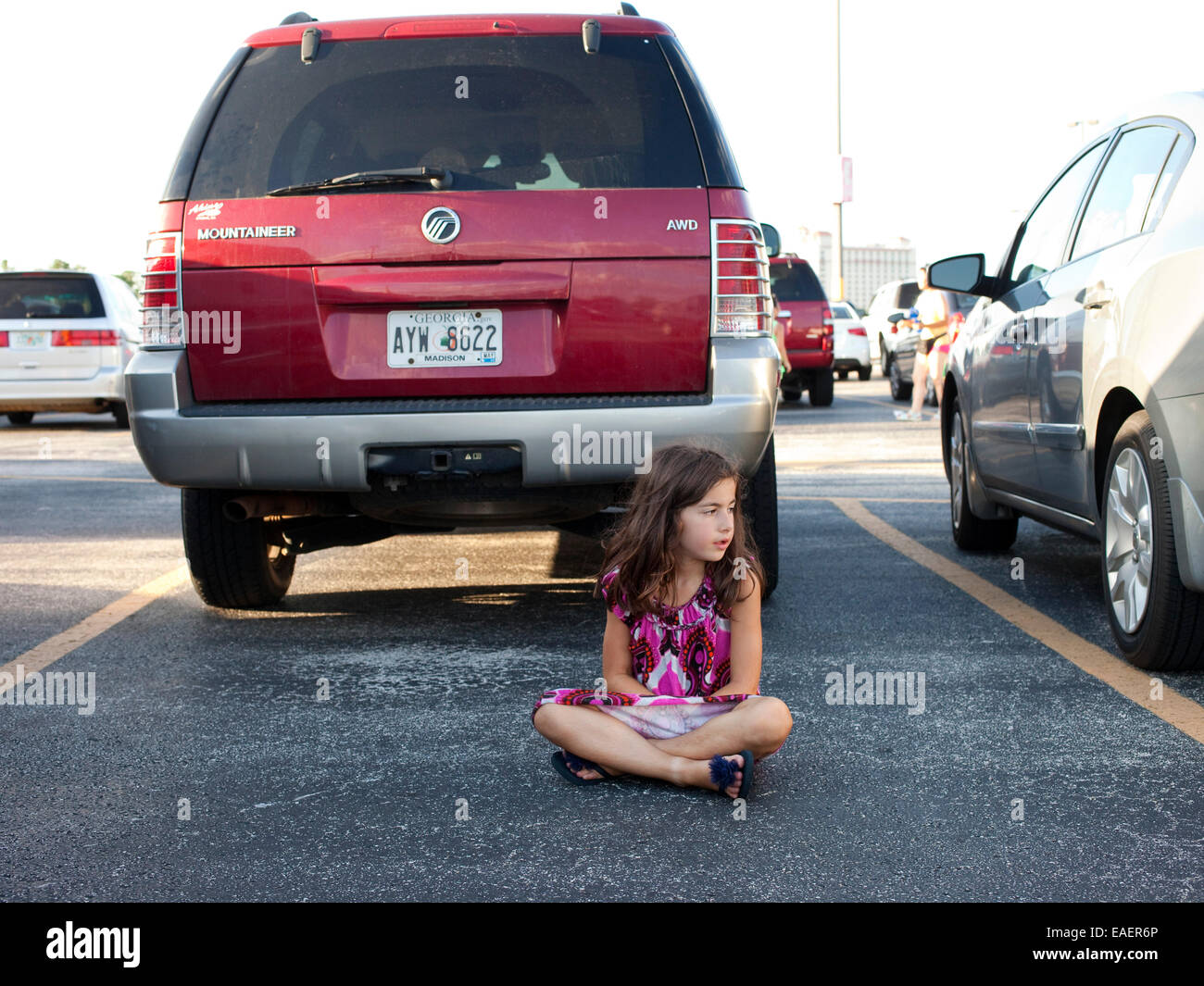 A young girl in a colorful dress sits in a parking lot and waits Stock Photo