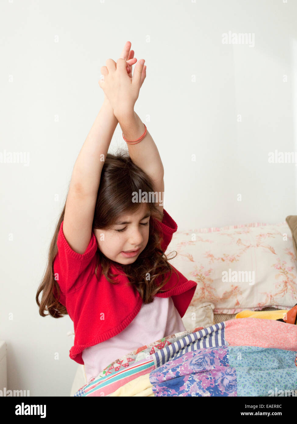 young girl waking up and stretching in bed - Stock Image