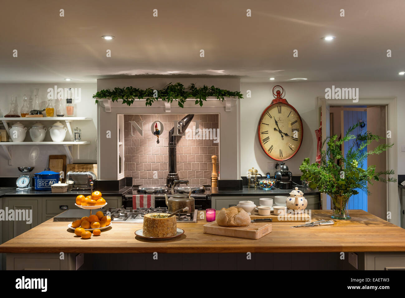 Cheese, bread and satsumas on wood topped butchers island in kitchen with aga and large red wall clock from Graham - Stock Image