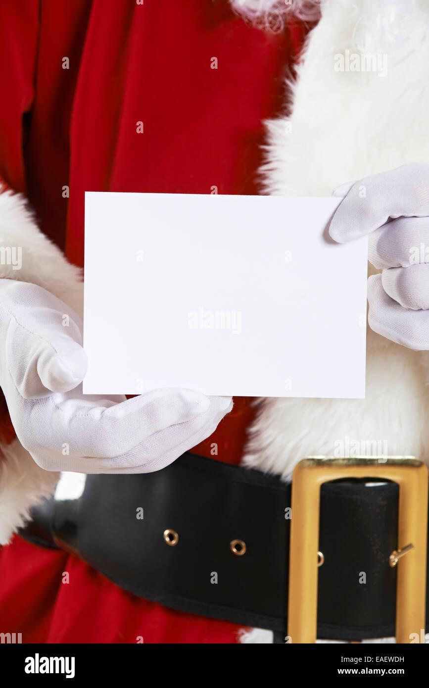 Close Up Of Santa Claus Holding Blank Invitation - Stock Image