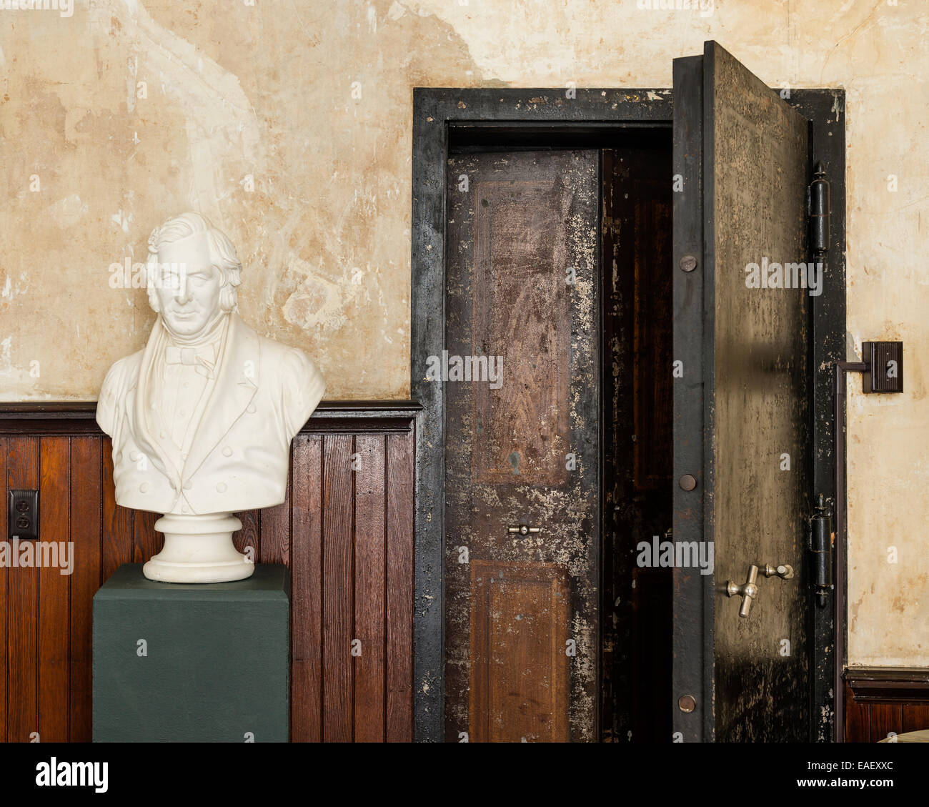 Plaster bust on green plinth in room with wooden wall panelling and large walk-in safe - Stock Image