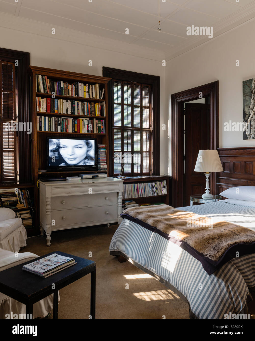 Flat screen tv above Swedish style chest of drawers in bedroom with ...