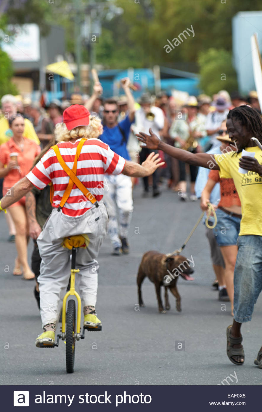 A clown on a unicycle hi-fives a smiling negro pedestrian as he passes by, during the 'gasfield free northern - Stock Image