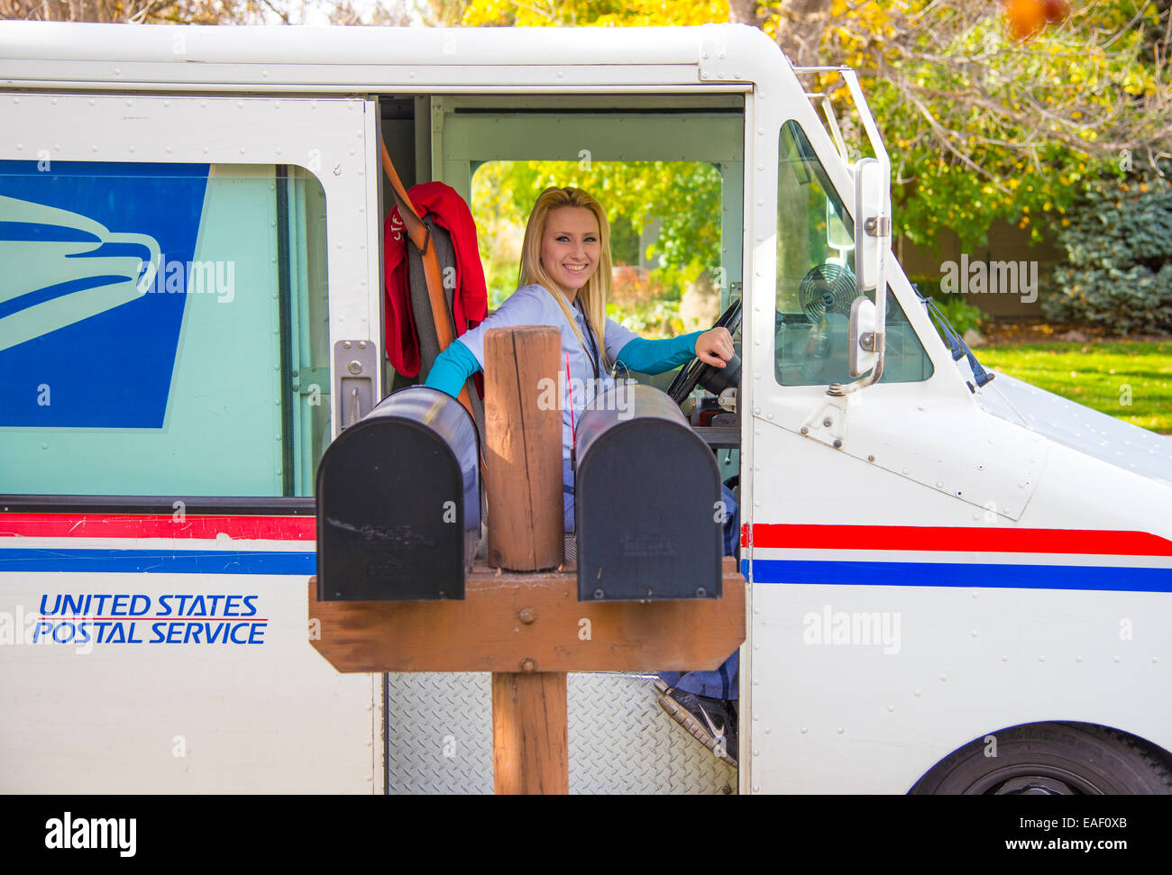 Female United States Postal Service carrier delivering mail in residential neighborhood. Boise, Idaho, USA - Stock Image