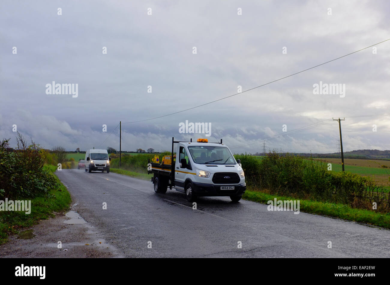 tradesmen vehicles on a wet country lane in Bedfordshire - Stock Image