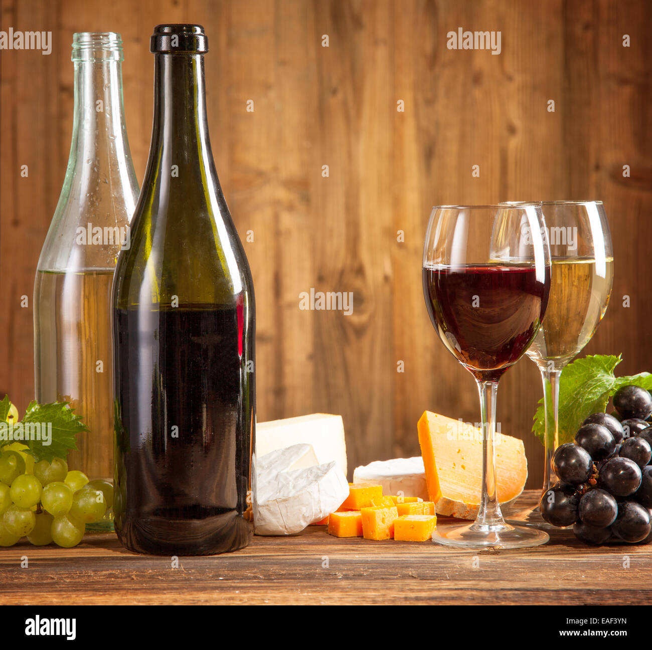 Wine with grapes and cheese on wooden planks - Stock Image