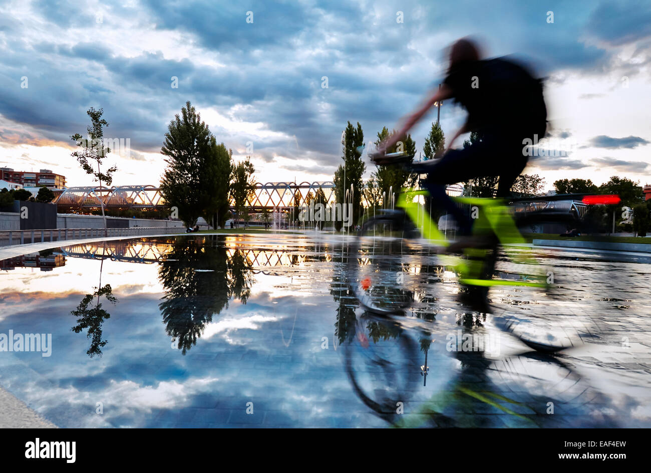 Cyclist passing by the pools and fountains in Madrid Rio Park. Madrid. Spain Stock Photo