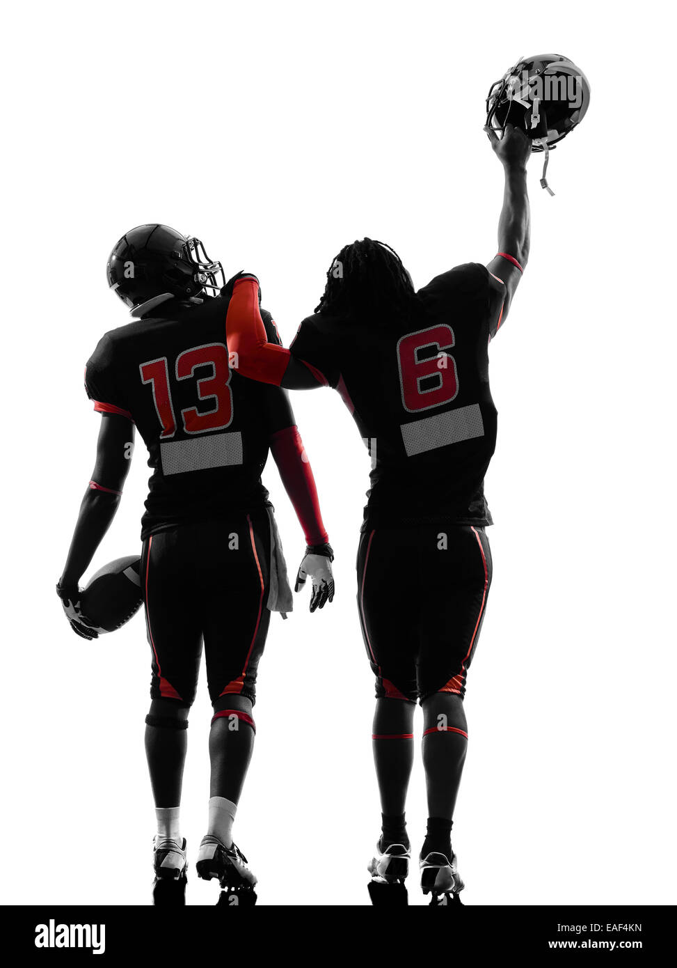 two american football players walking,rear view in silhouette shadow on white background - Stock Image
