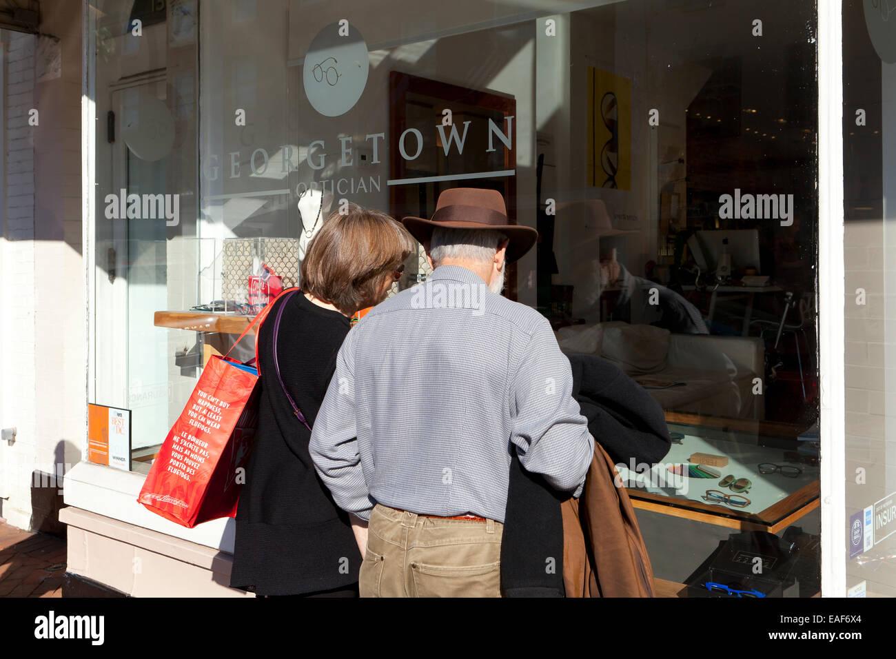 Elderly couple looking through optician store window - USA - Stock Image