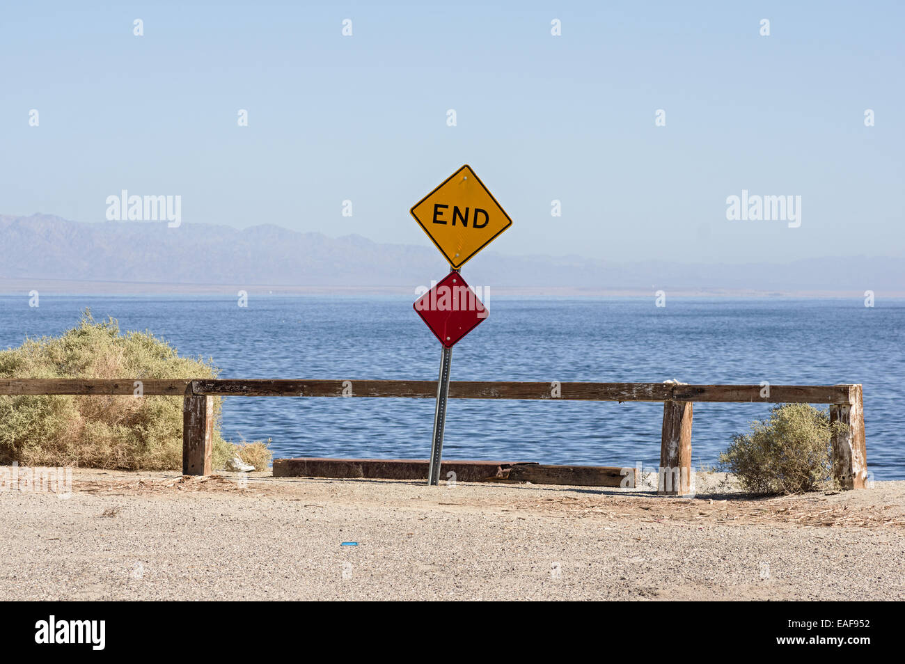 the end of the road where a road dead ends into the Salton Sea with a sign and barrier - Stock Image