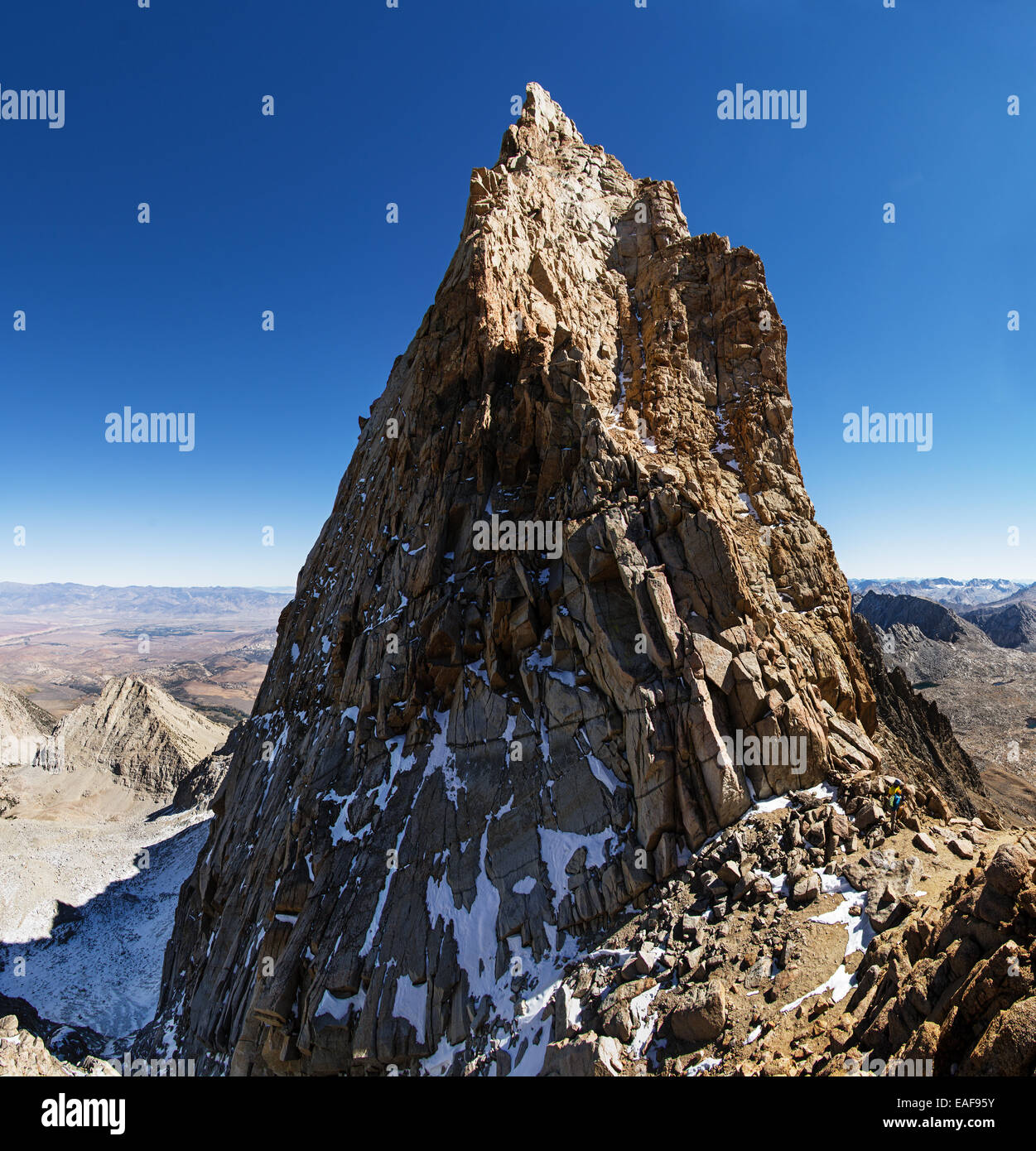 Mount Humphreys summit spire in the Sierra Nevada Mountains with two mountaineers at the base - Stock Image