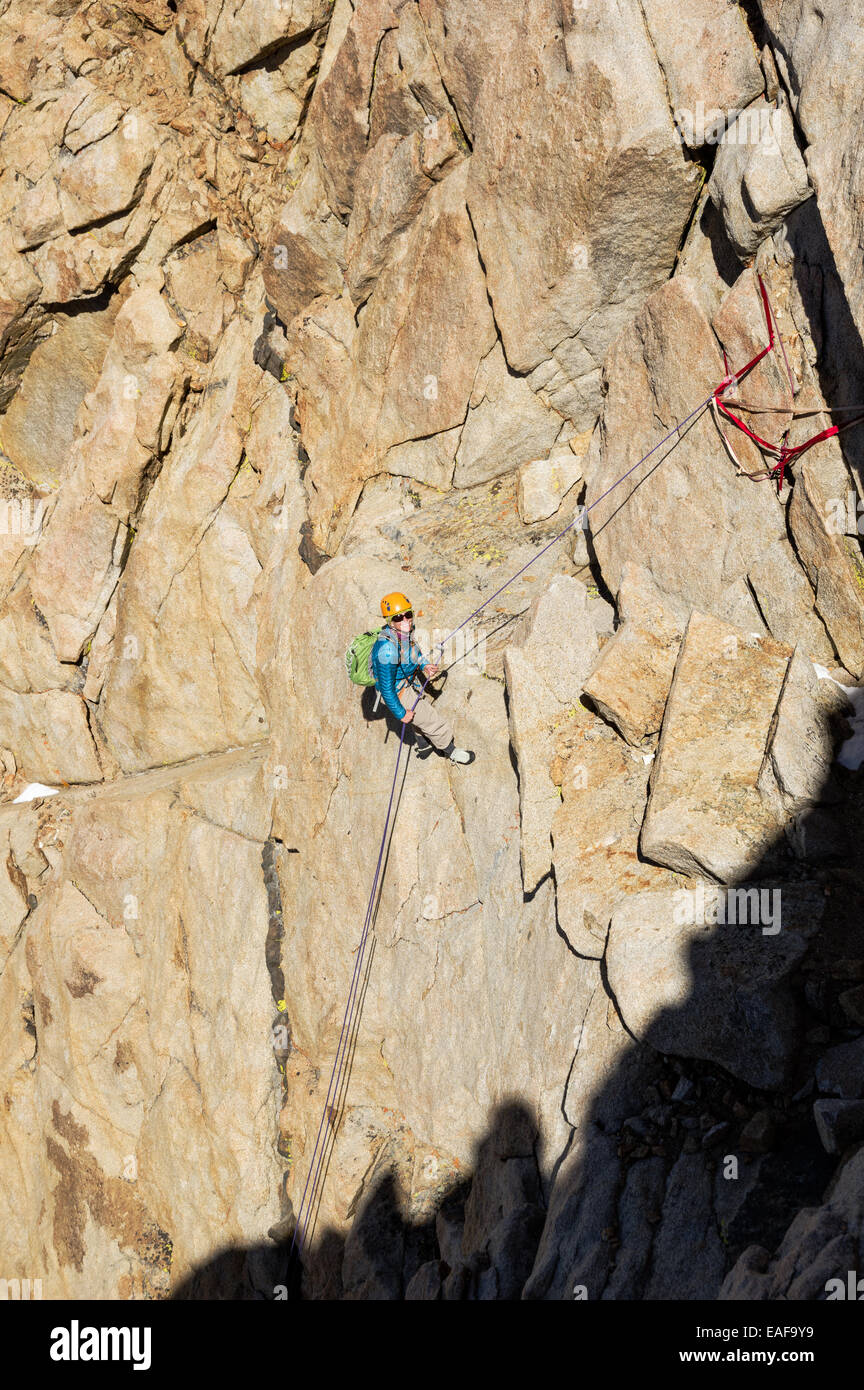 woman mountaineer rappelling down a mountain cliff - Stock Image