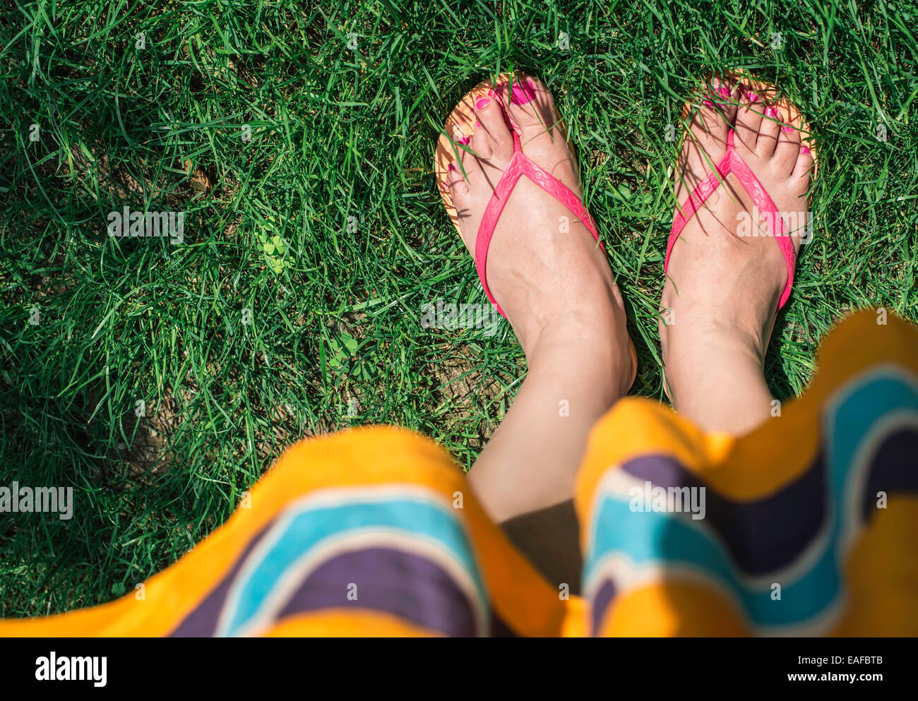 Feet on green meadow. Day light - Stock Image