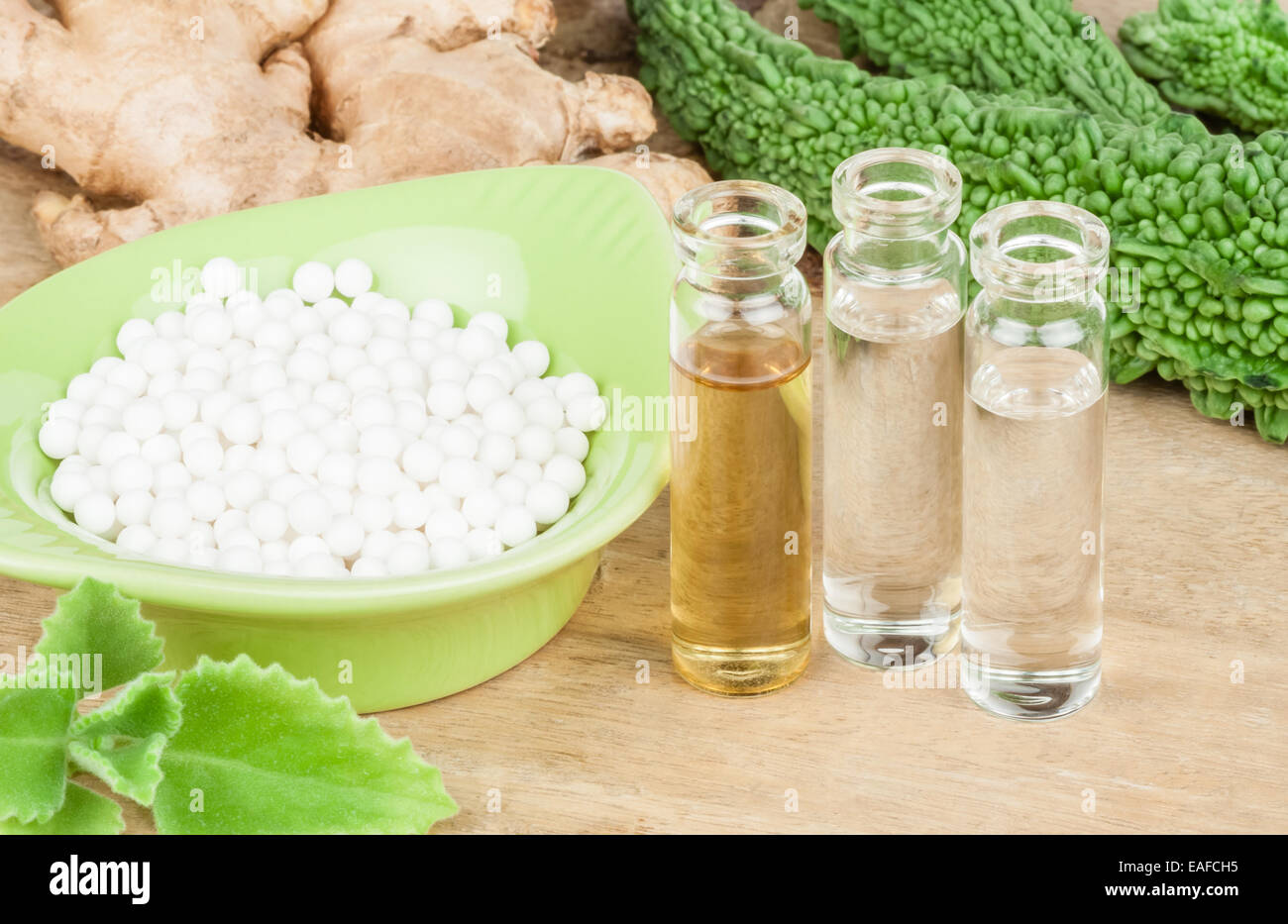 A homeopathy concept with homeopathic medicine pictured along with homeopathic vegetables and herbs on a wooden - Stock Image