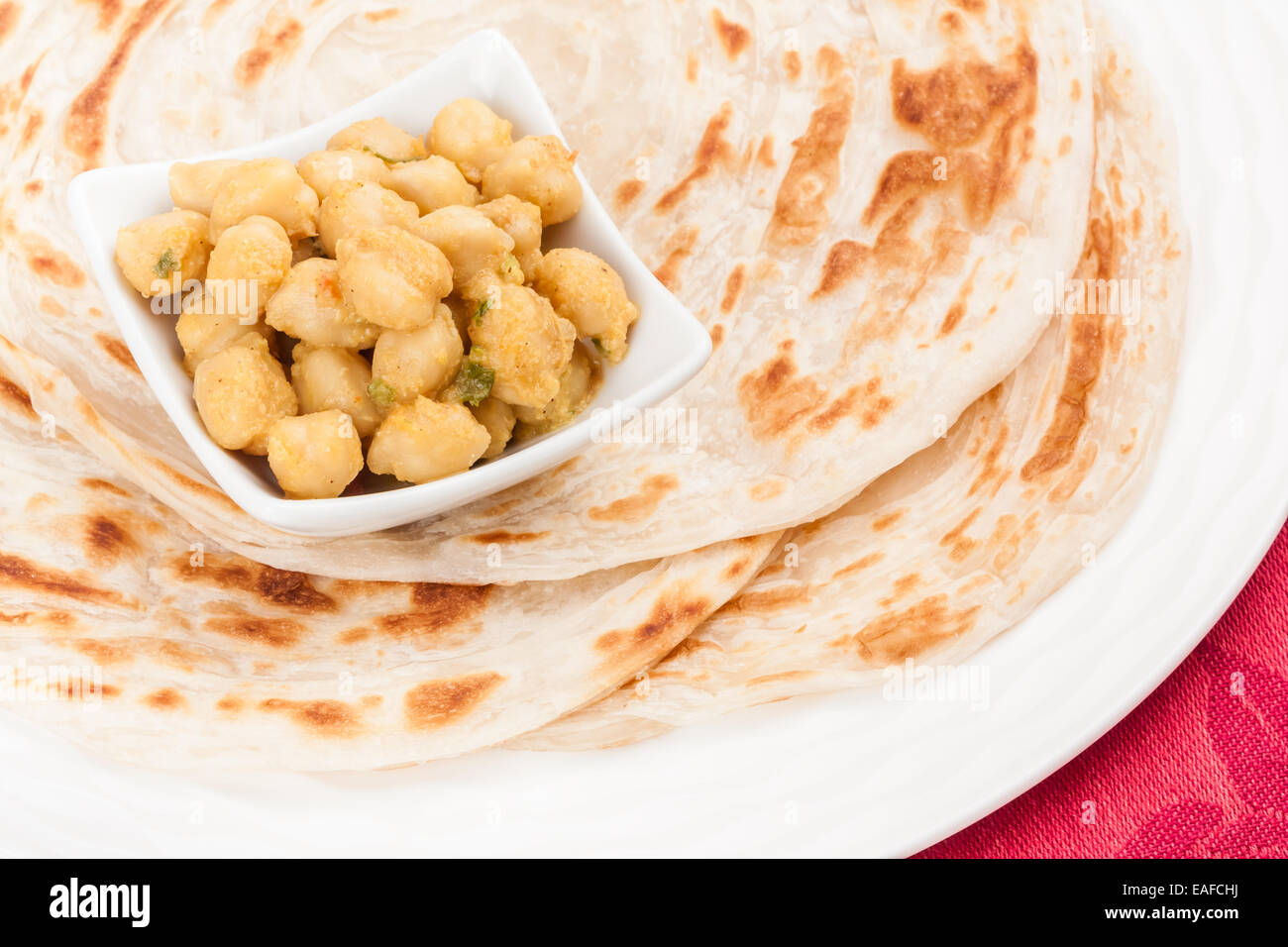 Homemade parotta (Indian bread) served with delicious Indian chana masala. It is prepared using chana dal and various - Stock Image