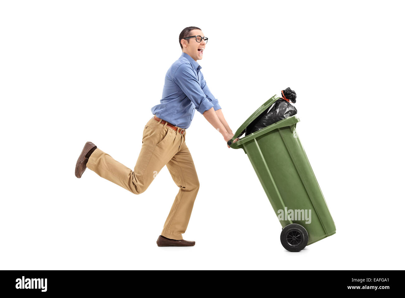 An excited man pushing a garbage can isolated on white background - Stock Image