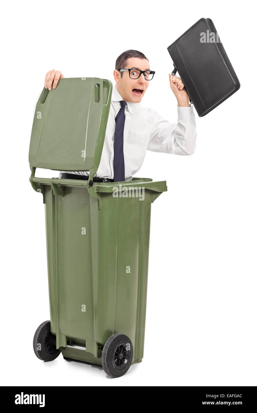 Terrified businessman hiding in a trash can isolated on white background - Stock Image