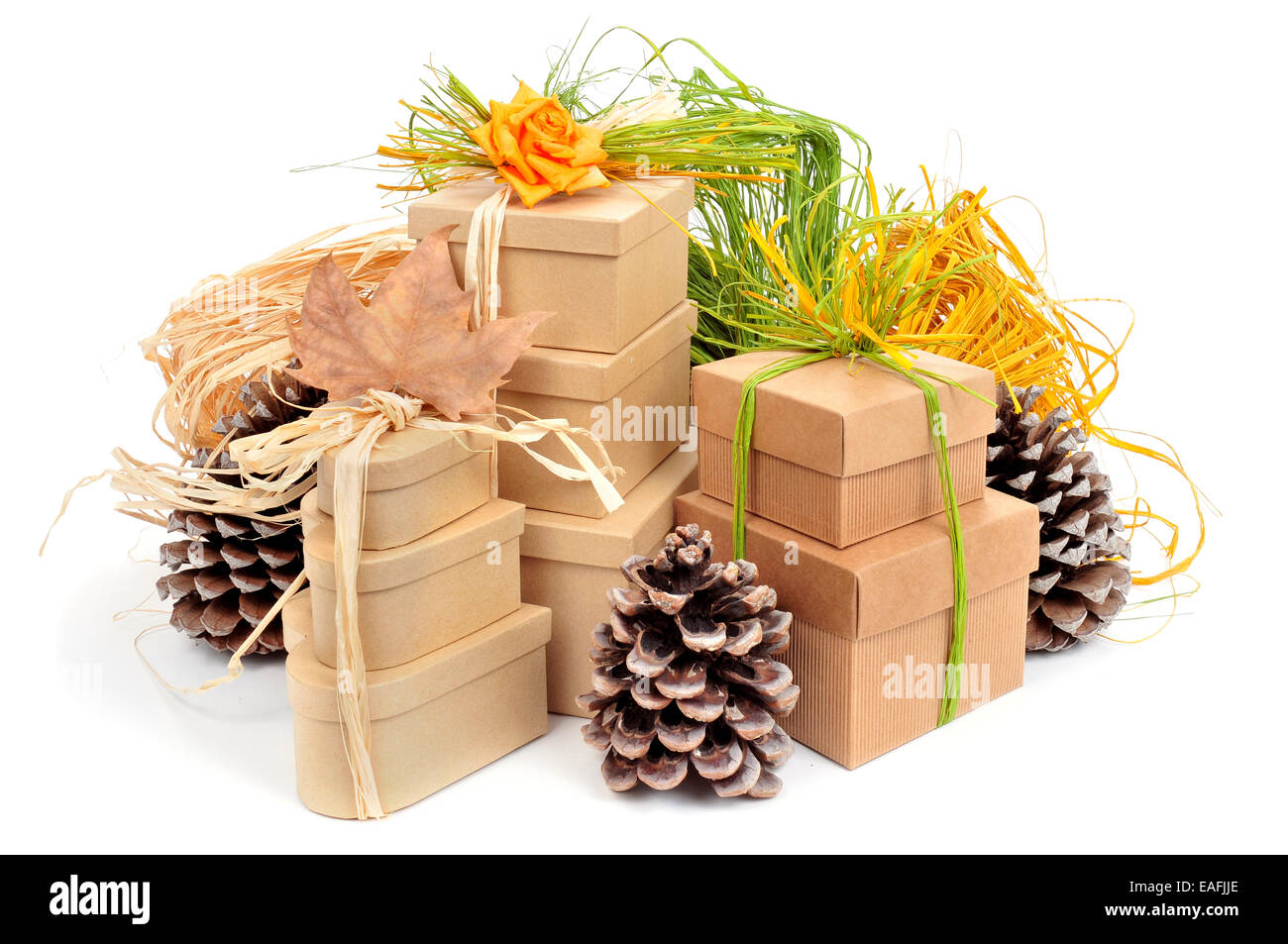 some gift boxes tied with natural raffia of different colors and surrounded by natural ornaments such as pinecones - Stock Image