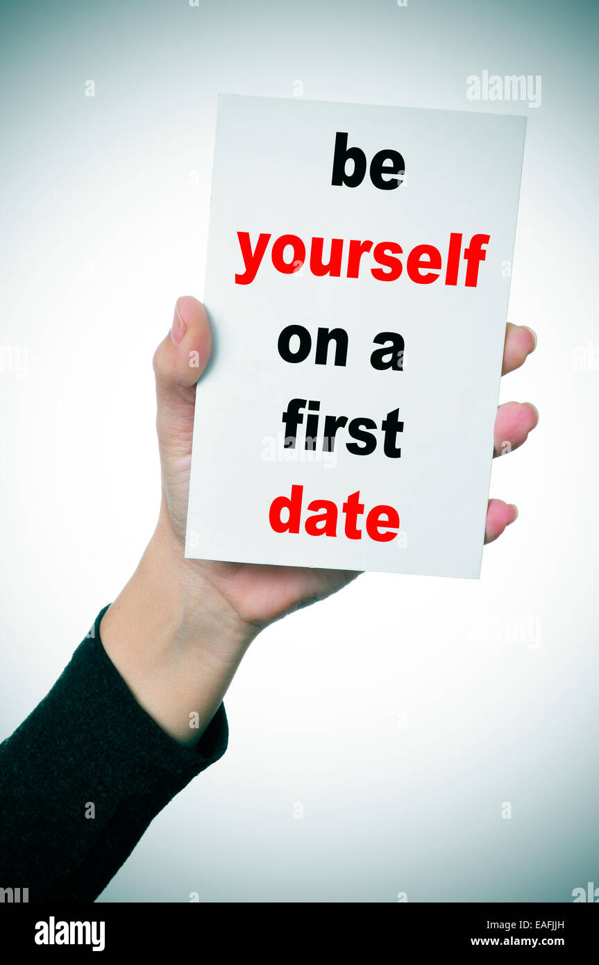 a woman hand showing a signboard with the text be yourself on a first date written in it - Stock Image