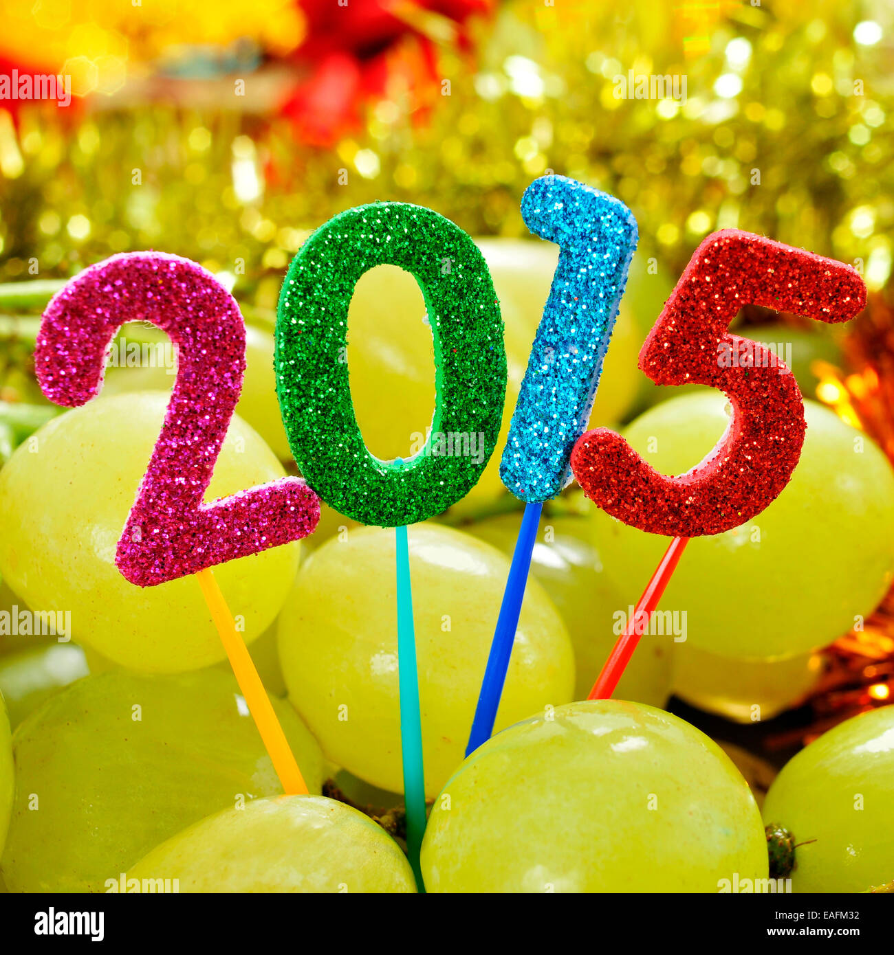 numbers of different colors forming the number 2015, as the new year, with a pile of grapes in the background - Stock Image