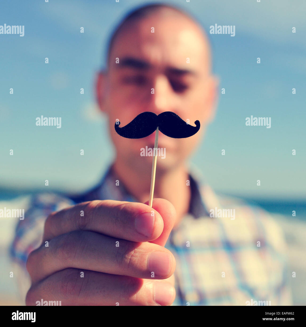 a young man holding a fake moustache in a stick in front of his face - Stock Image