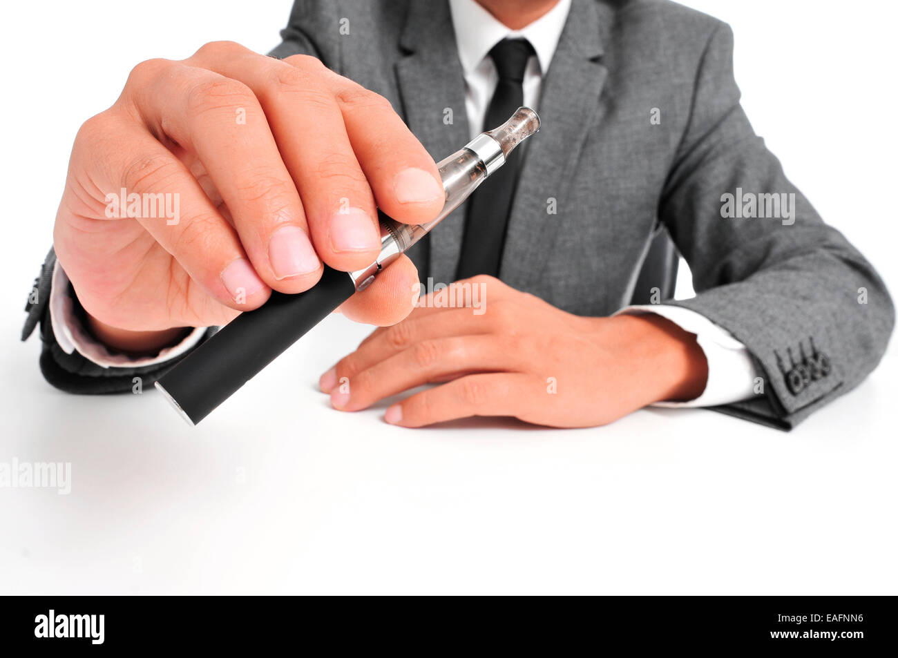 man wearing a suit vaping with an electronic cigarette - Stock Image