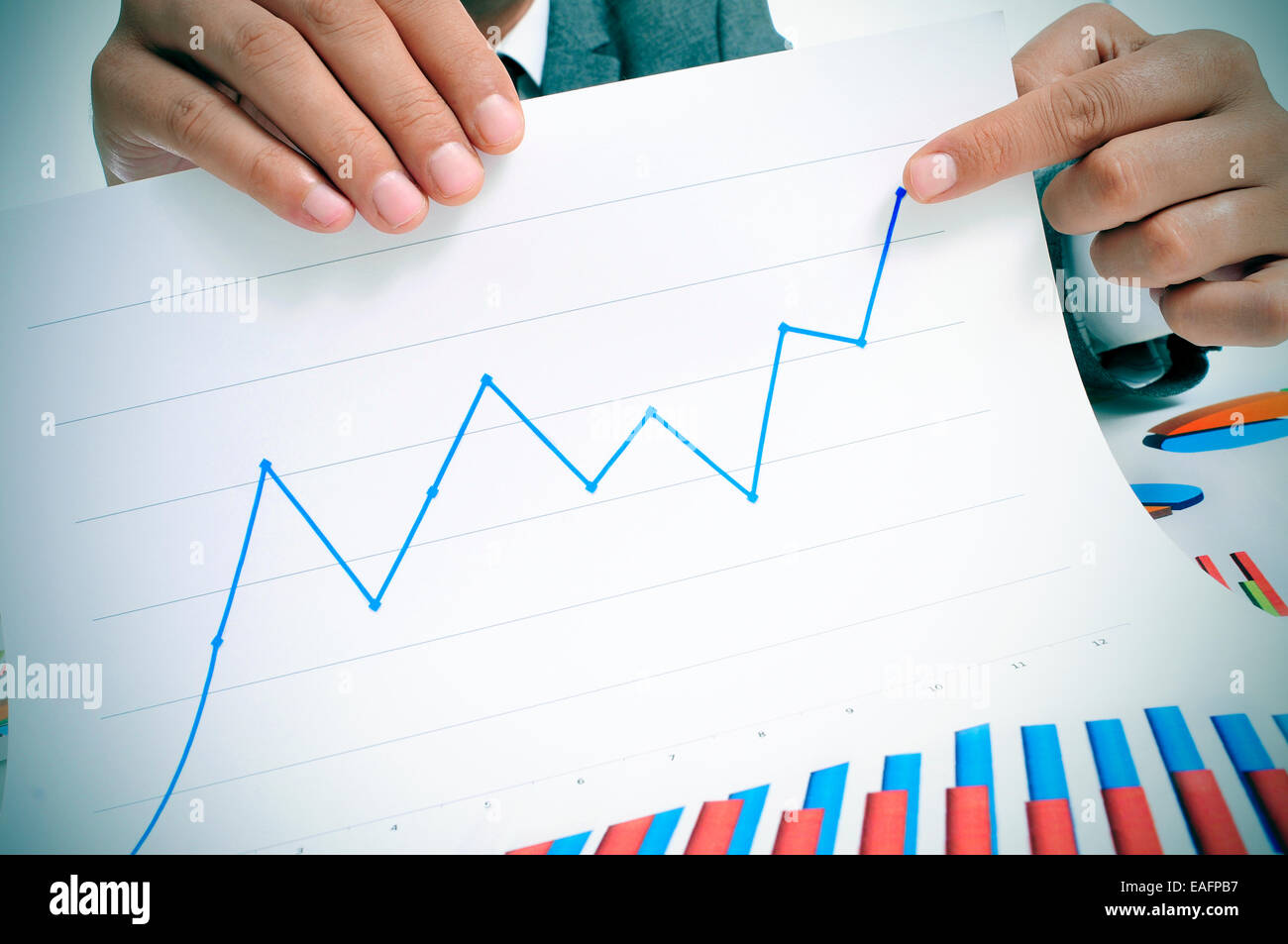 man wearing a suit sitting in a table showing a graph of economic growth - Stock Image