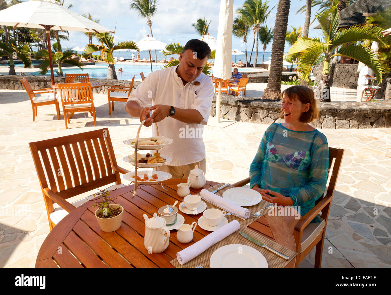 A woman guest being served afternoon tea at her table by a waiter, the luxury Residence 5 star hotel, Belle Mare, Stock Photo