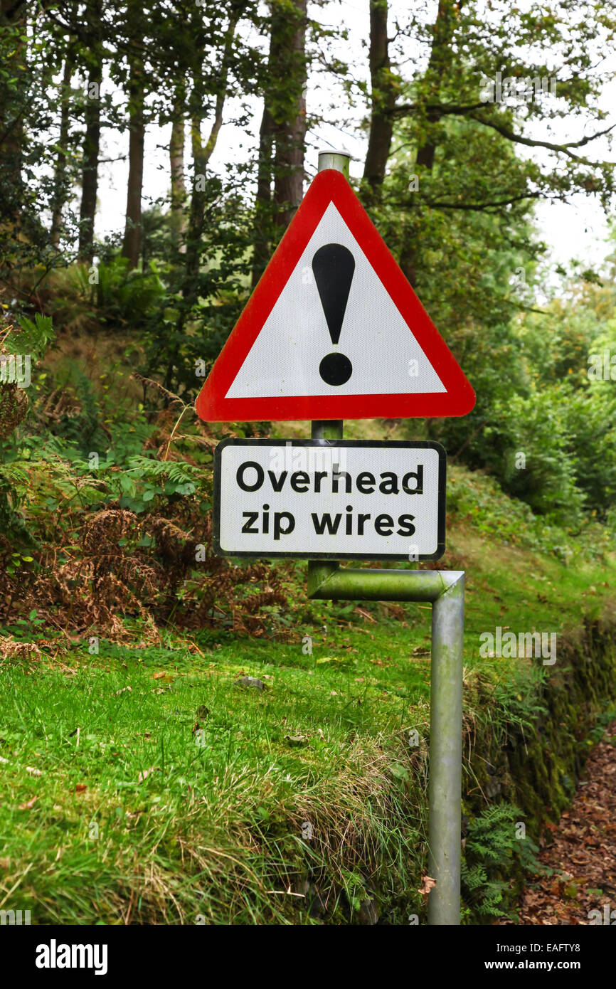 A road sign with an exclamation mark warning of overhead zip wires - Stock Image