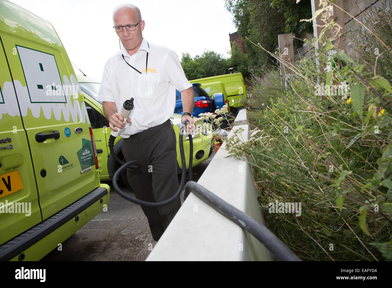 Man charges an electric van at a Brighton Council depot. - Stock Image
