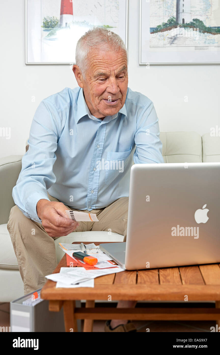 Senior sitting in front of a notebook and papers Stock Photo