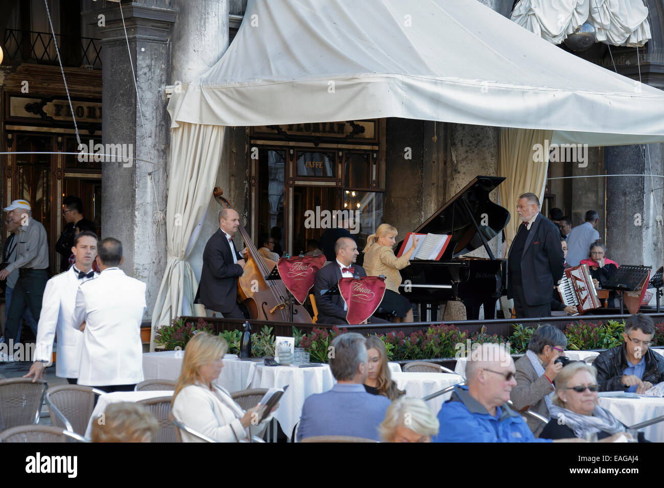 Orchestra, waiters and customers outside the Caffe Florian, Venice, Italy. - Stock Image