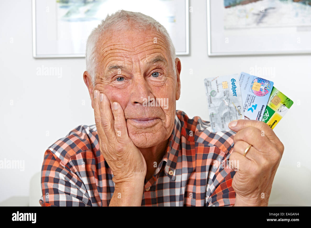 Senior with health insurance cards - Stock Image