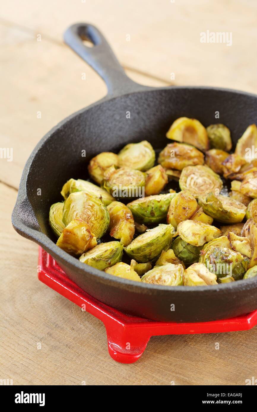 Roasted Brussels sprouts and chestnuts with a balsamic vinegar sauce in a cast iron skillet. Stock Photo