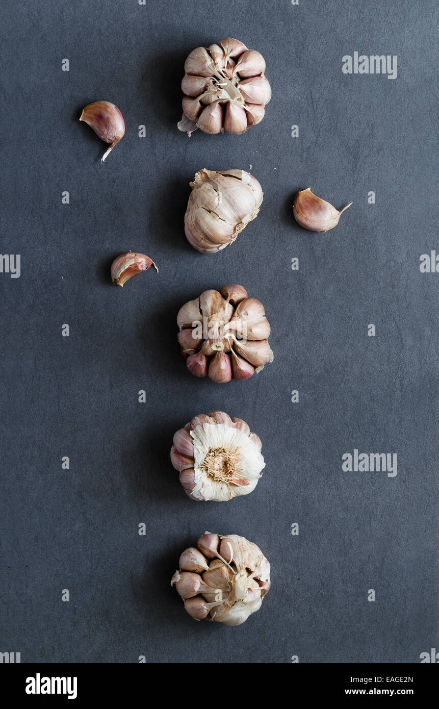 Cloves of garlic aligned in a row over dark blue table, above view - Stock Image