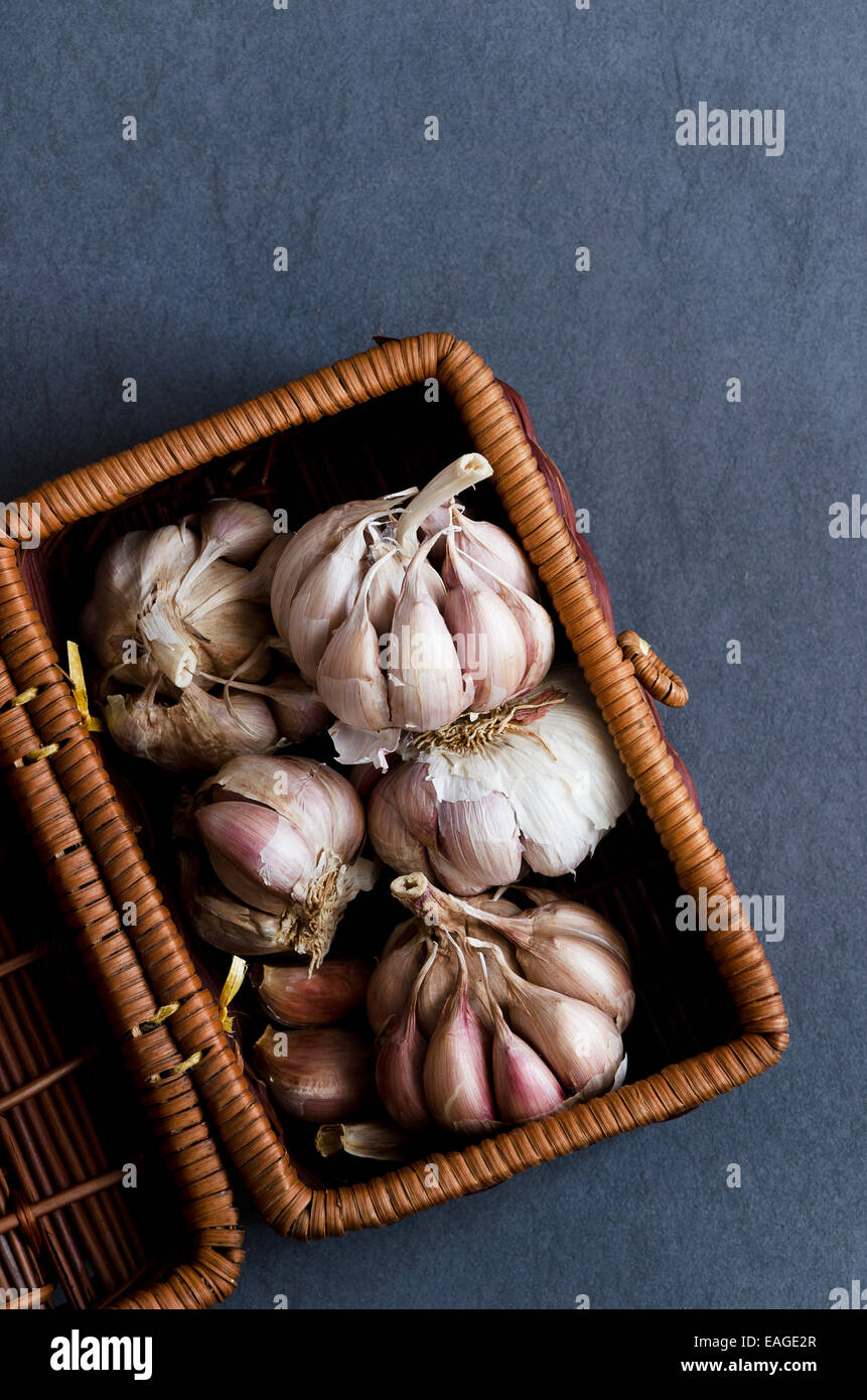 Cloves of garlic in a basket over dark blue table - Stock Image