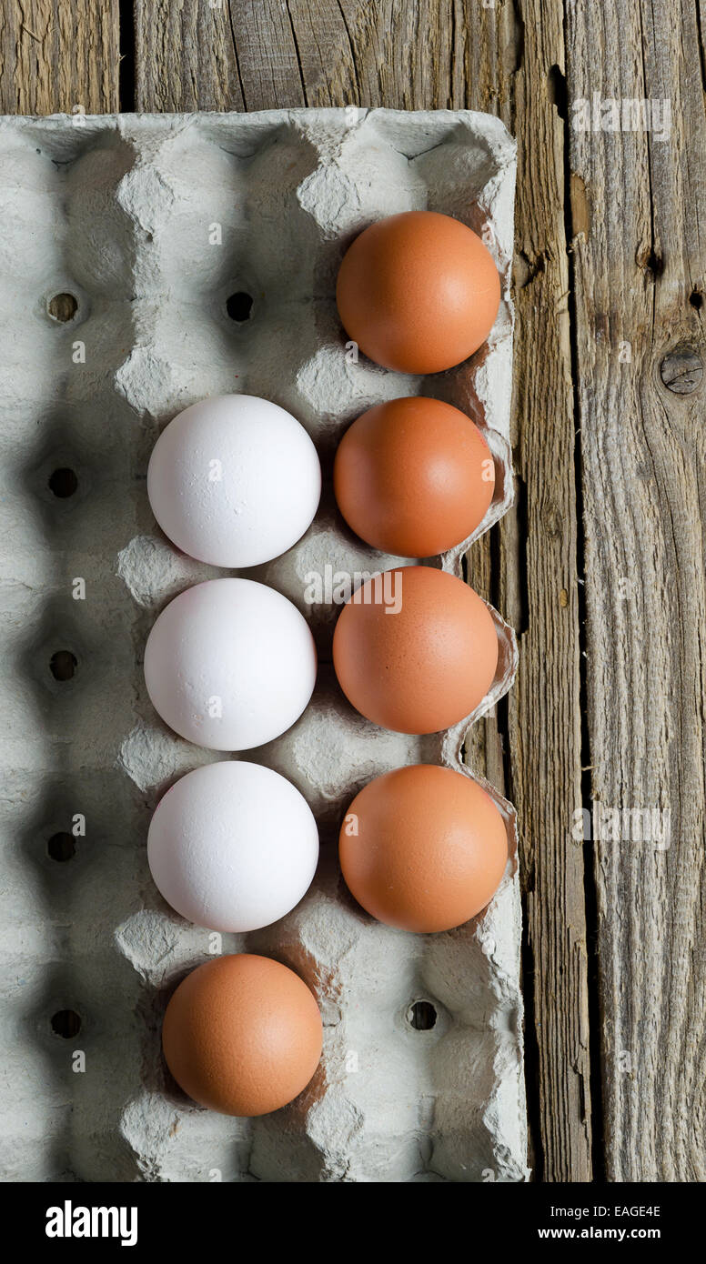 Eggs in formwork over wooden table - Stock Image